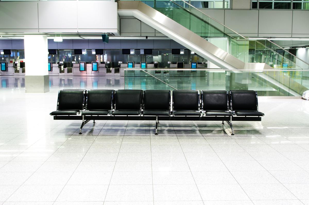 Im Wartebereich des Düsseldorfer Flughafen stehen schwarze Lederbänke