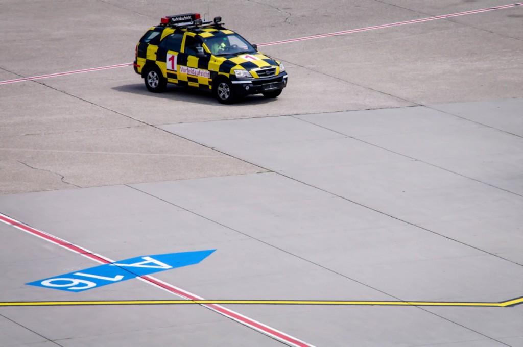 Startbahn des Düsseldorfer Flughafen mit einem schwarz-gelben Follow-me-car