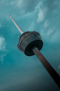 Vor türkisem Himmel ragt der Kölner Fernsehturm schräg ins Bild