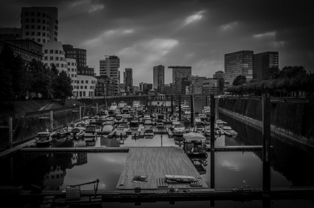 Schwarz-Weiß-Aufnahme des Düsseldorfer Medienhafen mit Hafenbecken und Ghery-Bauten