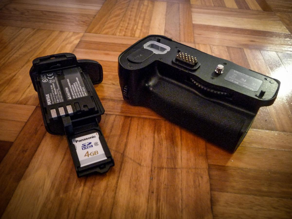Ein auseinandergebauter Batteriegriff mit Speicherkarte und Ersatzakku