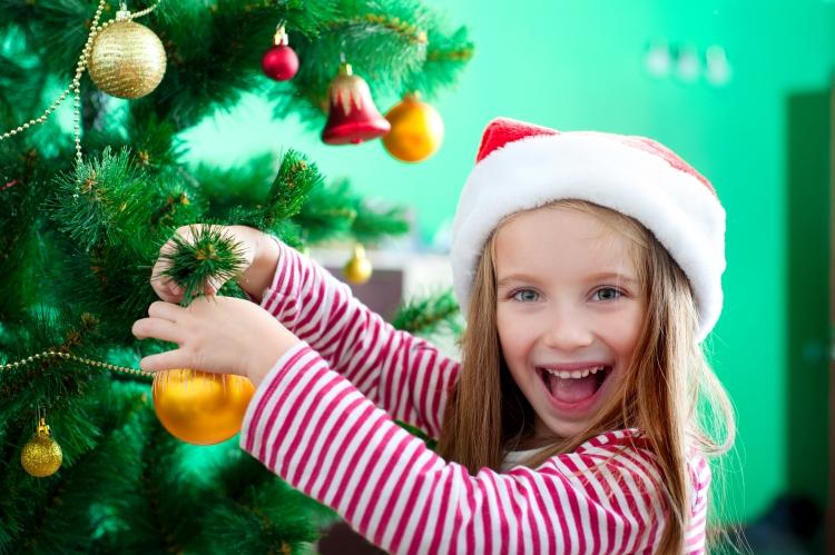 Portraitfotografie eines Mädchens an einem Tannenbaum