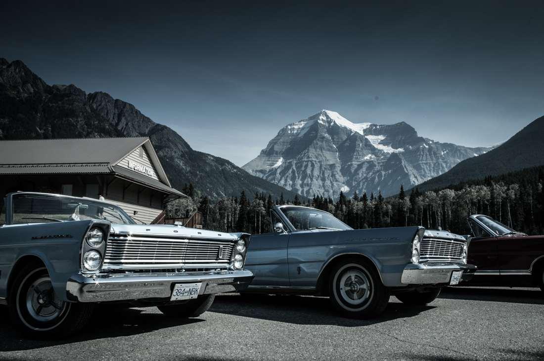 Eine Landschaftsfotografie von Oldtimern vor einem Berg in Kanada